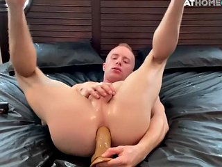 Smooth jock rides a huge dildo while jerking off in solo
